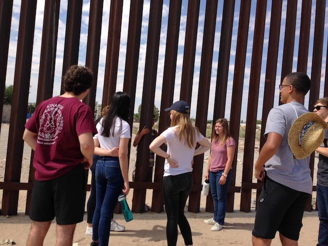 Students talk with residents of Mexico at the border fence in Texas.