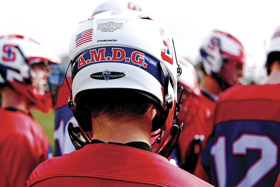 The letters A.M.D.G. on the back of a lacrosse helmet